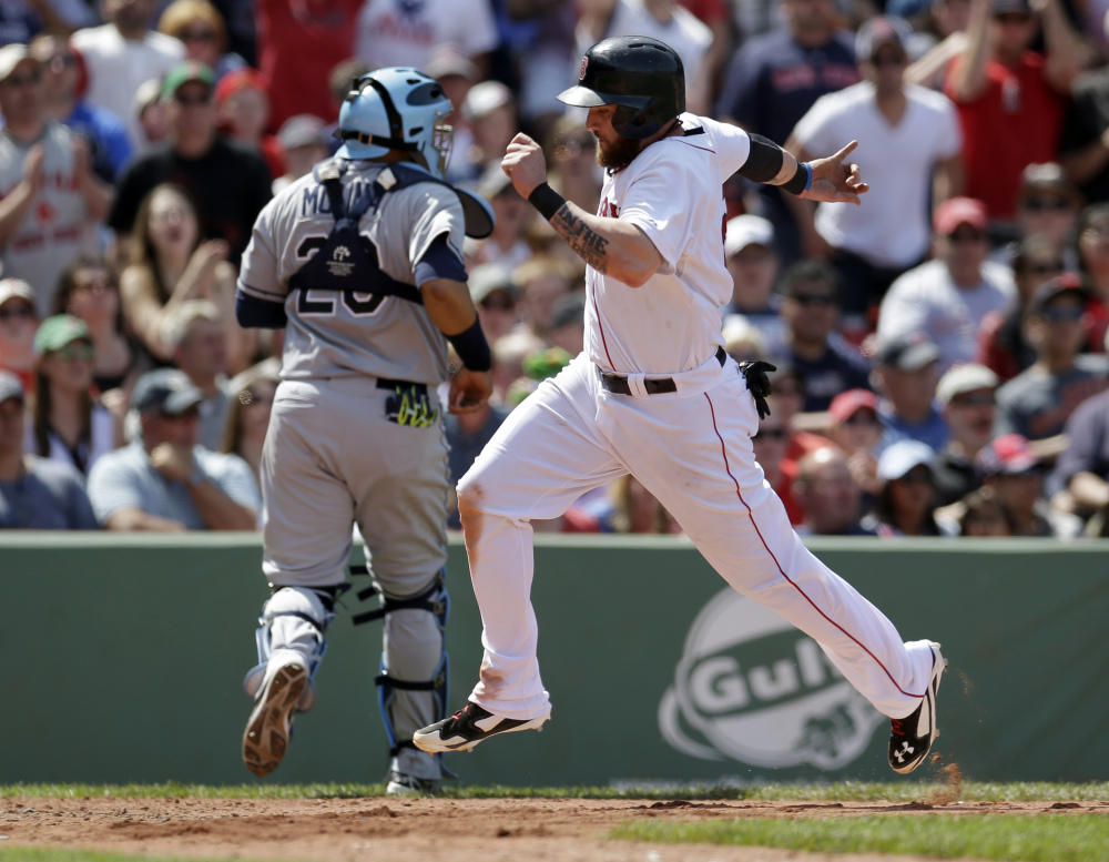 Boston Red Sox's Jonny Gomes, right, scores on a sacrifice fly as Tampa Bay Rays catcher Jose Molina, left, is unable to make the play in the fourth inning of a baseball game, Sunday, in Boston. The Associated Press