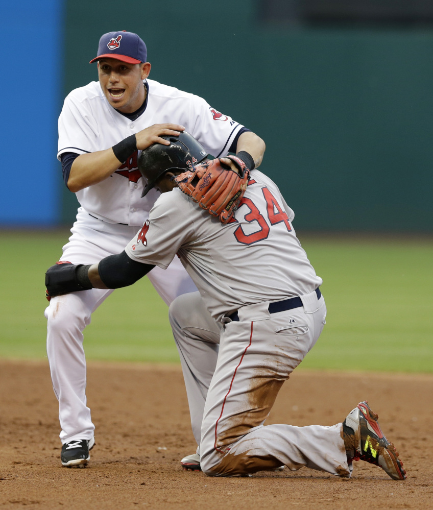 Cleveland Indians' Asdrubal Cabrera, top, holds onto Boston Red Sox's David Ortiz after Ortiz was out at second base on a double play in the third inning of a baseball game, Monday, June 2, 2014, in Cleveland. A.J. Pierzynski was out at first base. (AP Photo/Tony Dejak)