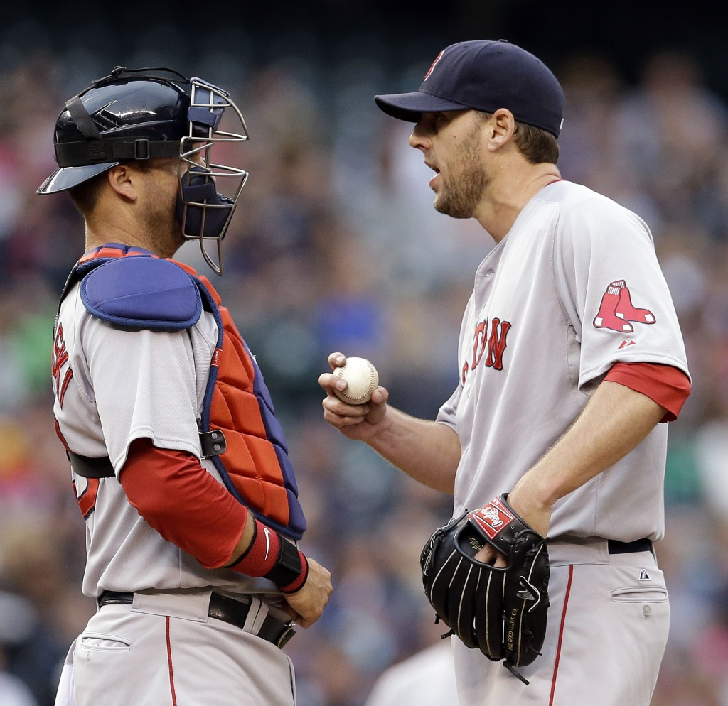 Boston Red Sox starting pitcher John Lackey talks with catcher A.J. Pierzynski after Lackey gave up a run to the Seattle Mariners in the fourth inning Monday in Seattle.