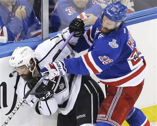 New York Rangers center Dominic Moore crashes the boards against Los Angeles Kings right wing Justin Williams in the third period of Game 4 of the NHL Stanley Cup Final on Wednesday in New York. The Rangers won the game 2-1. The Associated Press