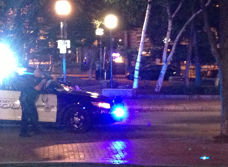 A Portland police officer aims a shotgun toward a Ford Escape on Exchange Street during a