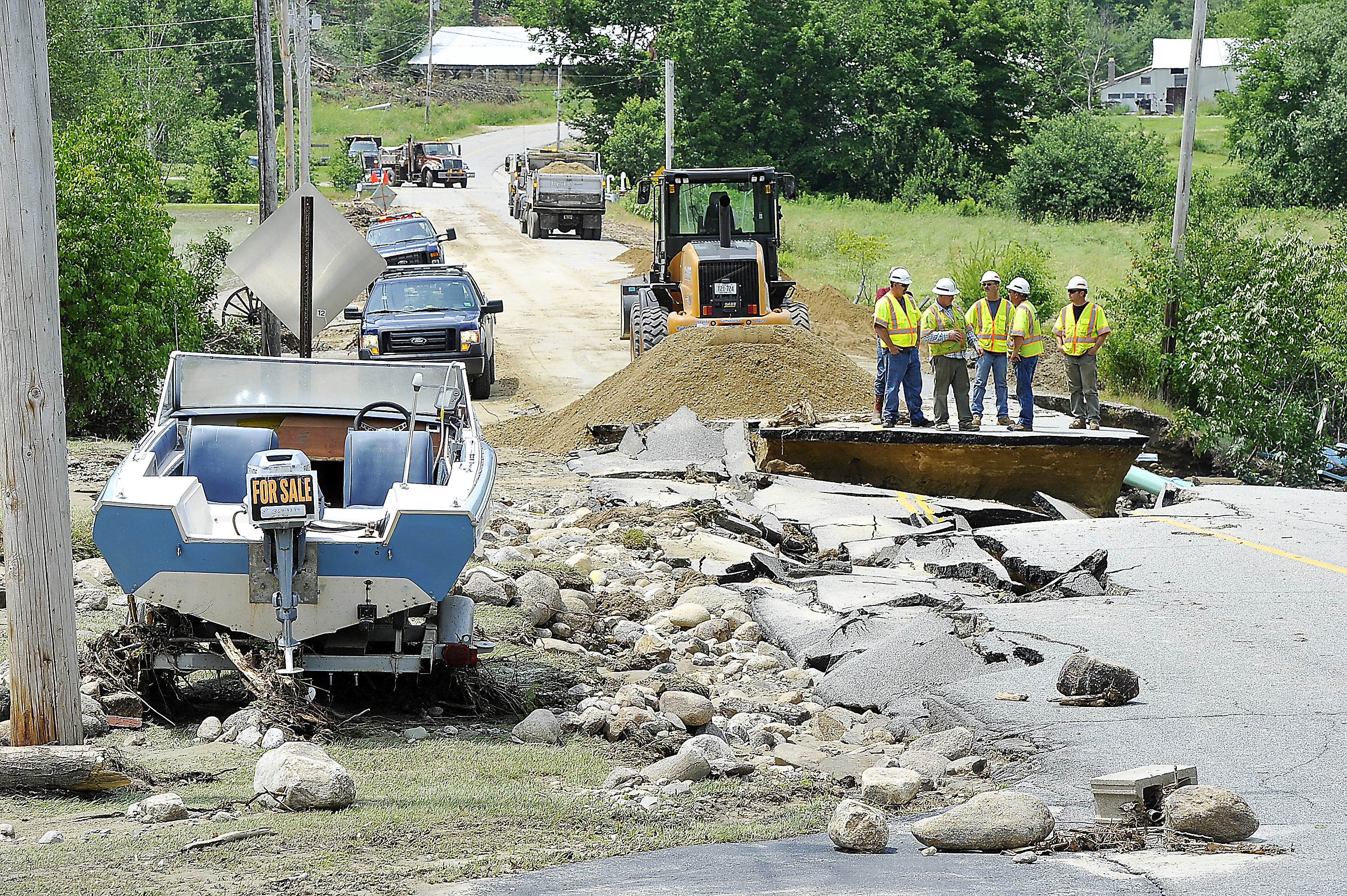 A boat for sale made it through the night of the heavy rains and winds in Rumford. A crew from the Maine Department of Transportation inspects the damage to South Rumford Road as they await more trucks of sand to make temporary repairs of the washed-out road.