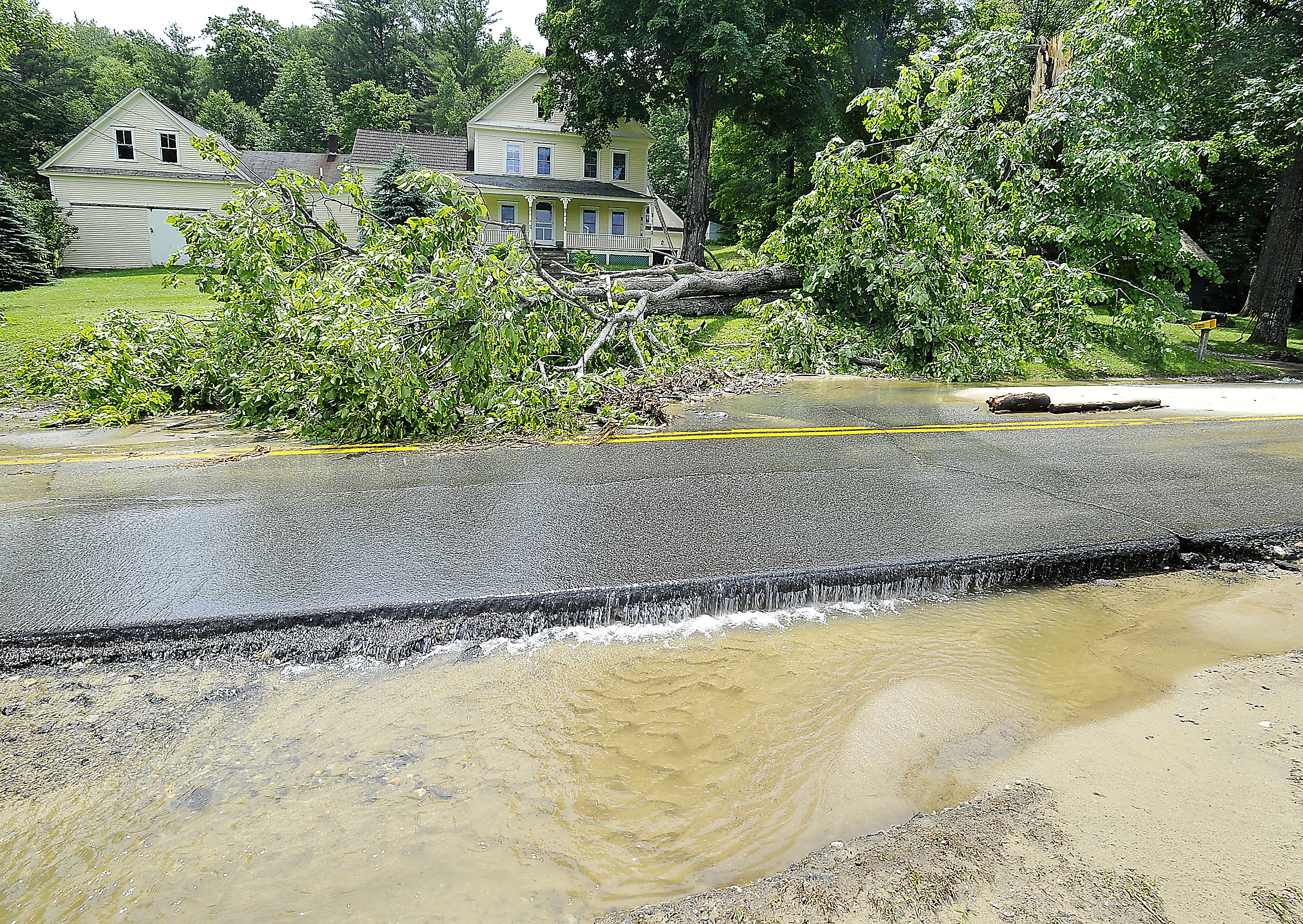 Water flows over the washed-out Wyman Hill Road in Rumford on Thursday. A tree came crashing down at the home of Karen Blanchard on Wednesday during the storms.