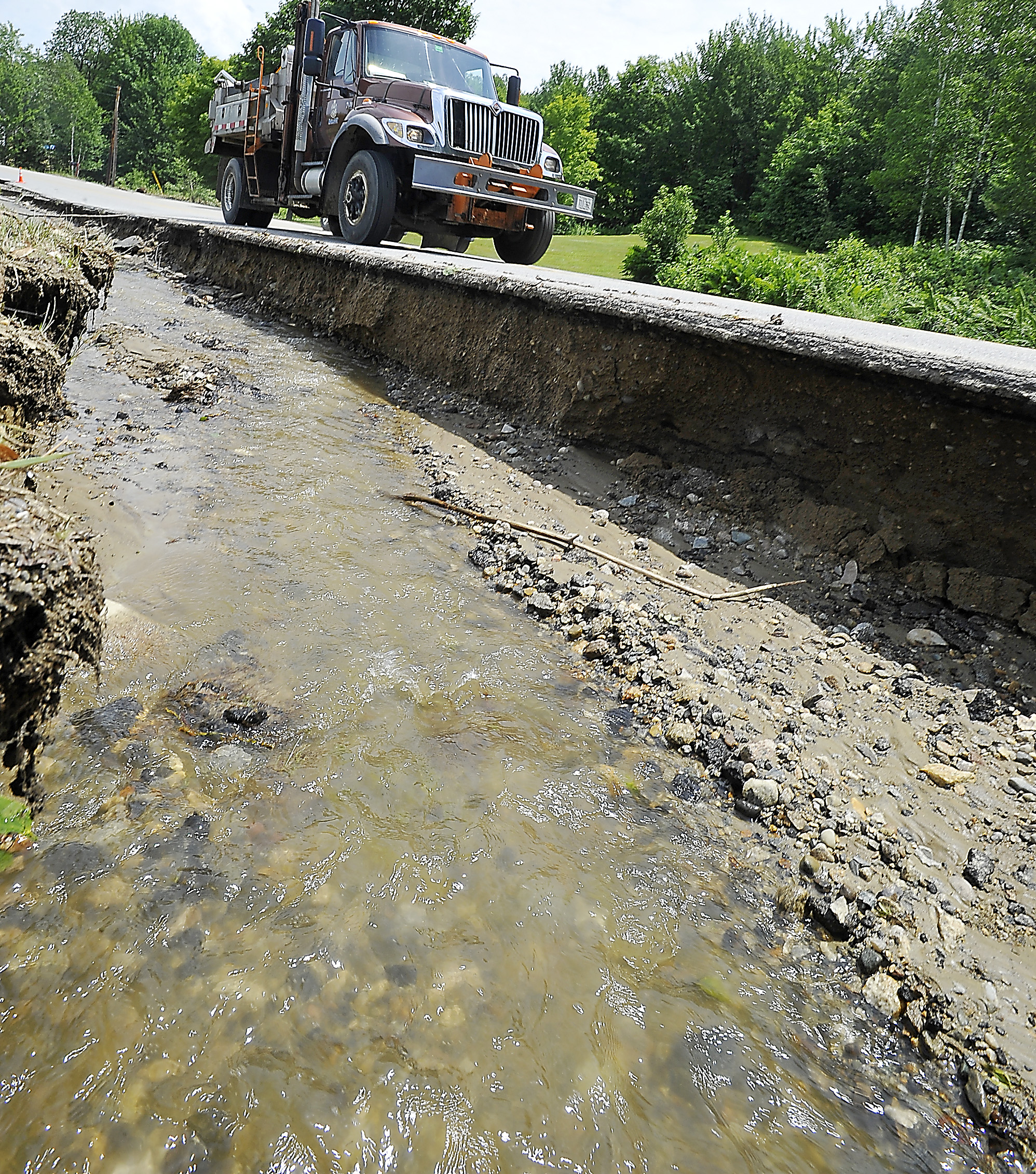 A truck filled with sand travels along the precarious edge of Wyman Hill Road in Rumford on Thursday as it heads for the most damaged part of South Rumford Road.