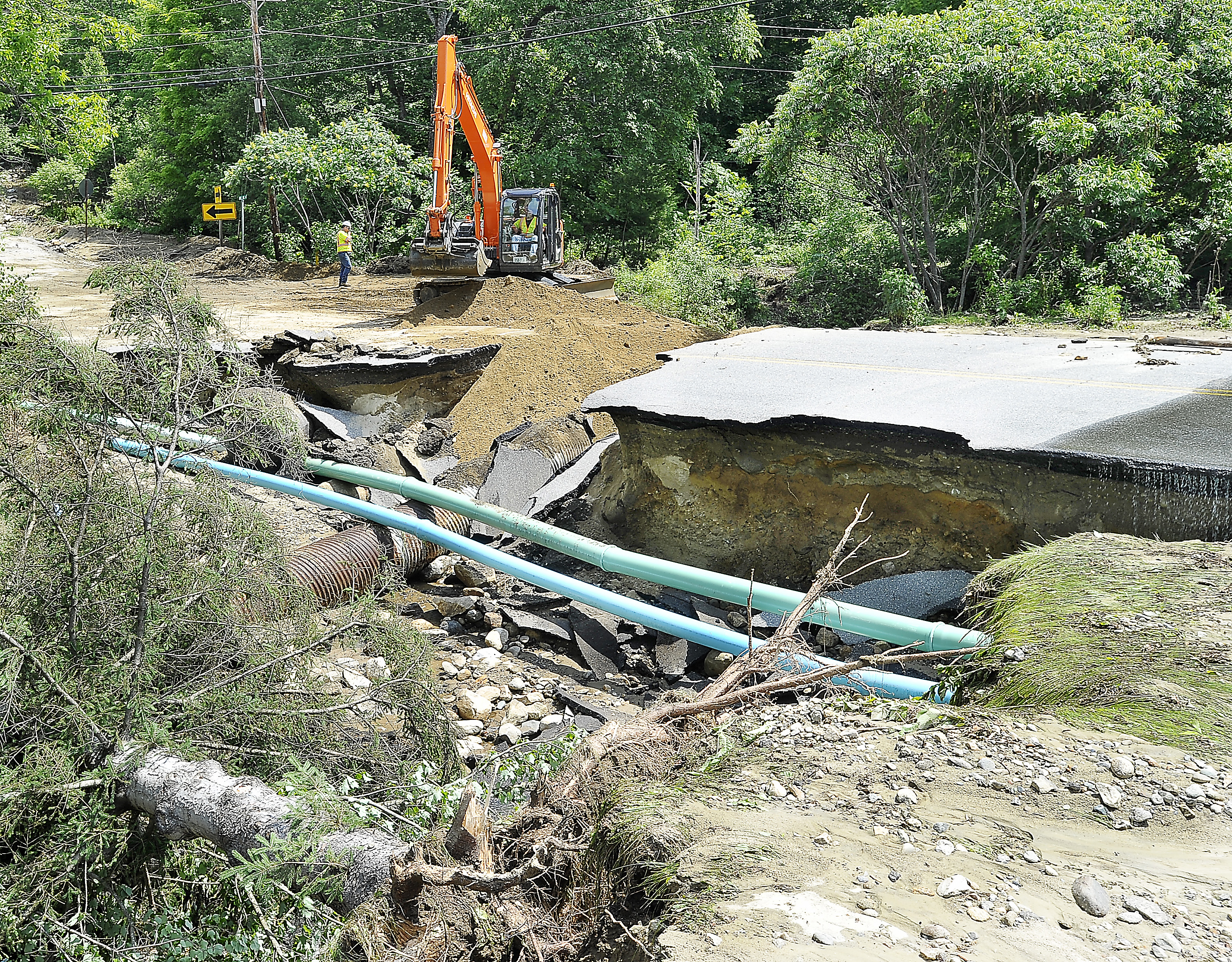 Sewer lines remain intact but the road is washed out on South Rumford Road in Rumford as a crew from the Maine Department of Transportation makes temporary repairs Thursday.