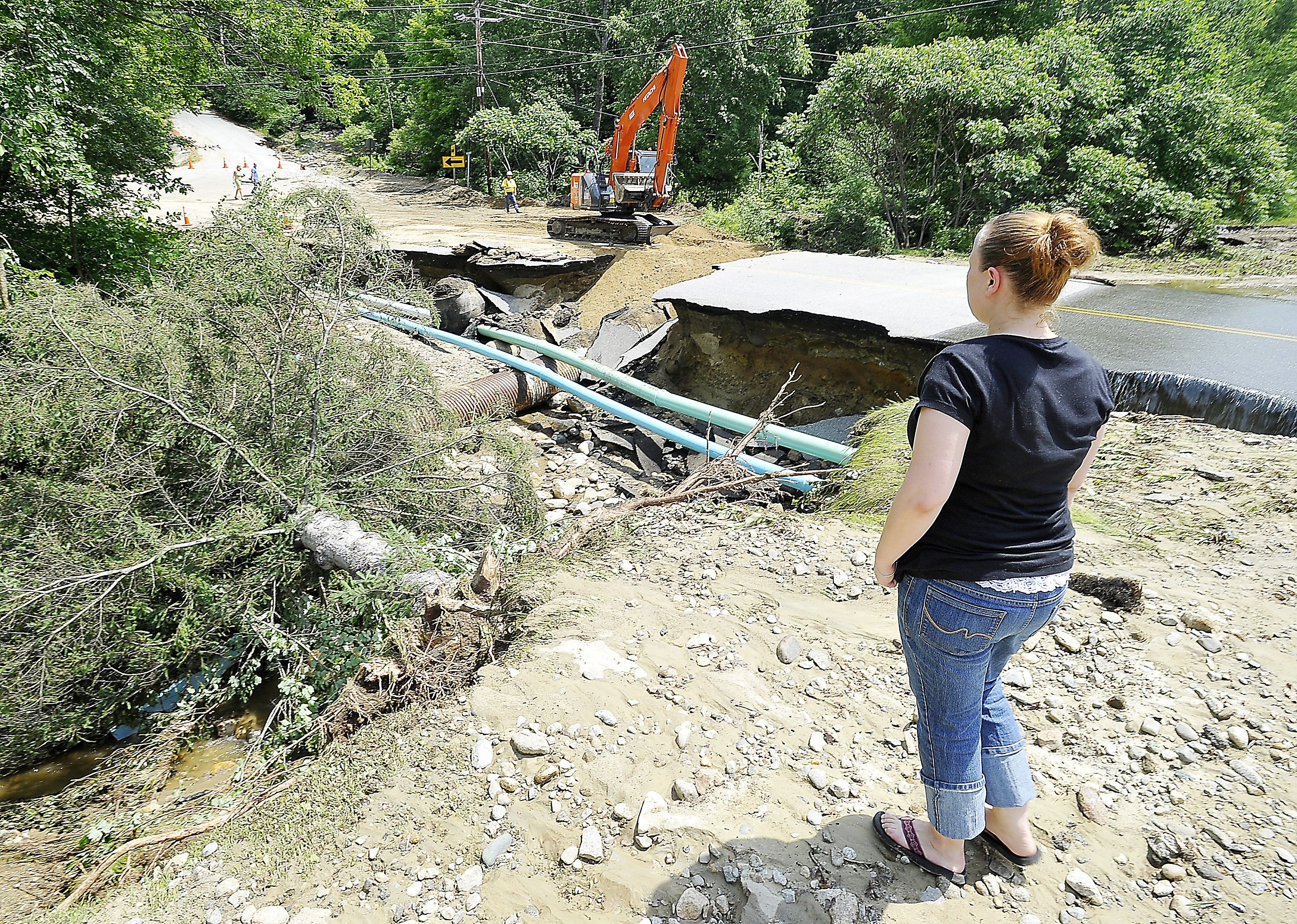 Rumford resident Sophie Post on Thursday looks at what used to be her garden and a large fir tree that tumbled into the washed-out gorge carved by  flood waters the previous night as  a crew makes temporary repairs .