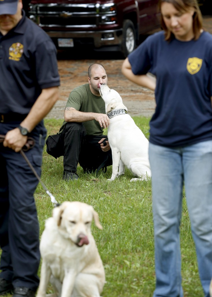 Tom Accoglio of the Gloucester County Sheriff's Department in New Jersey receives a kiss from his arson dog Roxy, 3, during the annual State Farm arson dog program recertification class at the Yarmouth Fire Department training facility Tuesday.