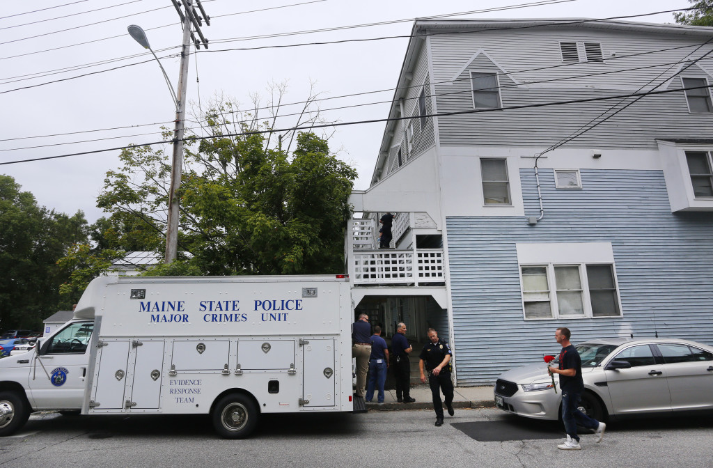 A man carrying flowers arrives at 23 Water St. in Saco, where Maine State Police are investigating the discovery of five bodies Sunday afternoon. Derek Davis/Staff Photographer