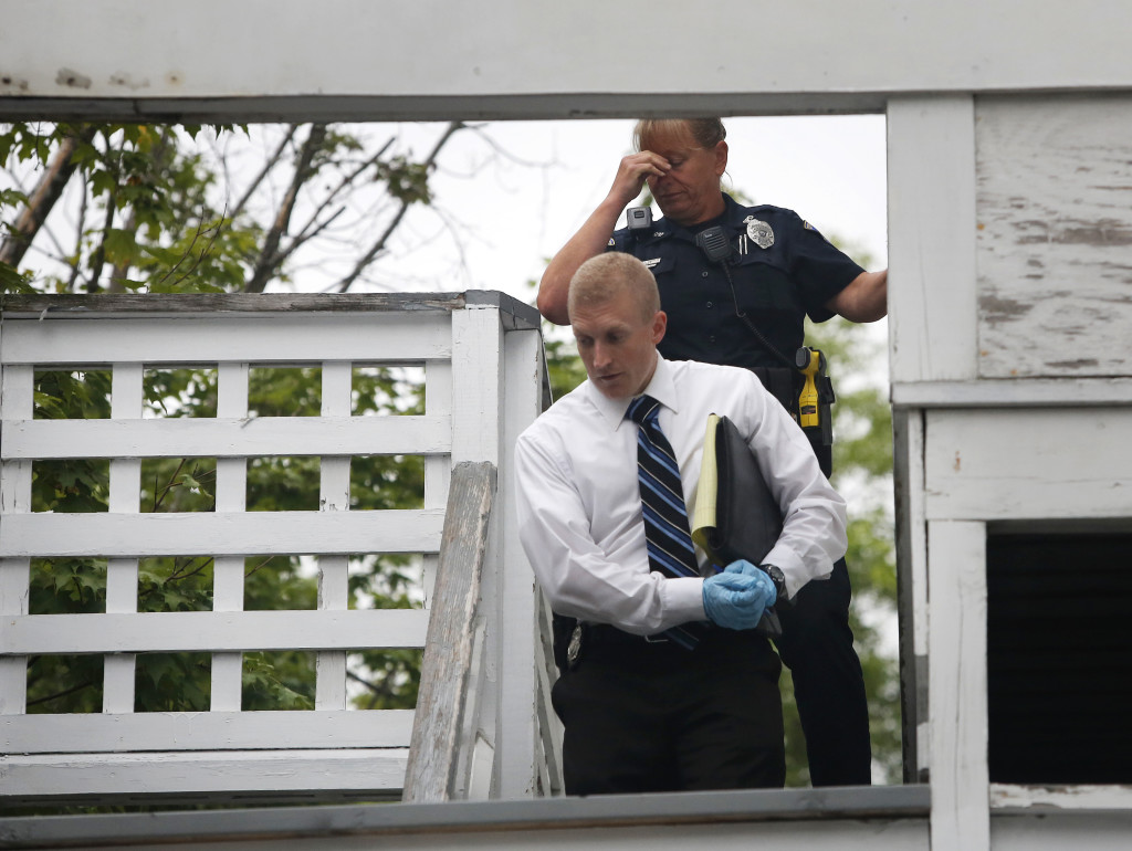 An investigator leaves the apartment at 23 Water St.in Saco where Maine State Police are investigating the deaths of a man, woman and three children. Derek Davis/Staff Photographer