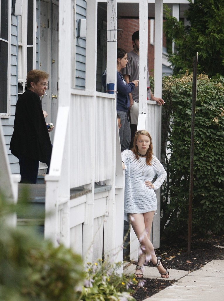 Neighbors watch from across the street as police investigate the deaths of a family of five in a Water Street, Saco, apartment Sunday. Jill Brady/Staff Photographer