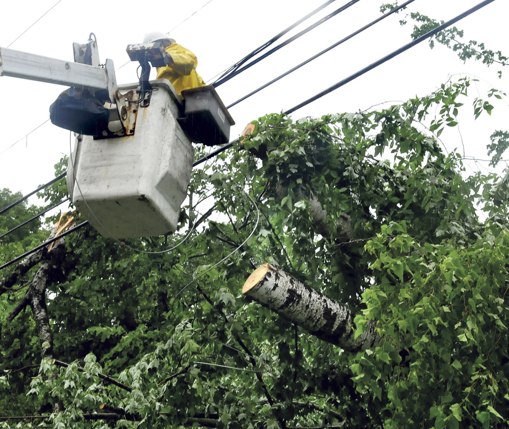 Nelson Stevens of Next Gen company works from a bucket near trees that topped onto wires along Corinna Road in St. Albans and cutting off power on Wednesday.