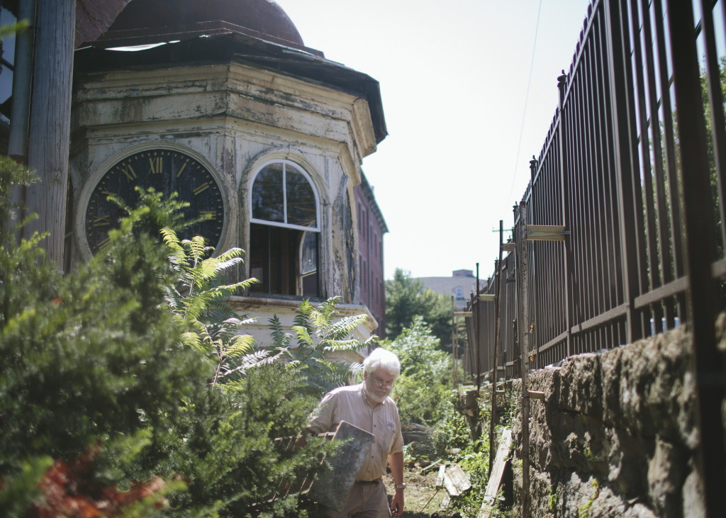 "George Collord walks through the Pepperell Mill Campus where the Lincoln Mill clock tower is currently housed in Biddeford. ""Seeing this clock tower eventually move, it's a symbolic resurgence of everything that's best about this place."" Whitney Hayward / Staff Photographer"
