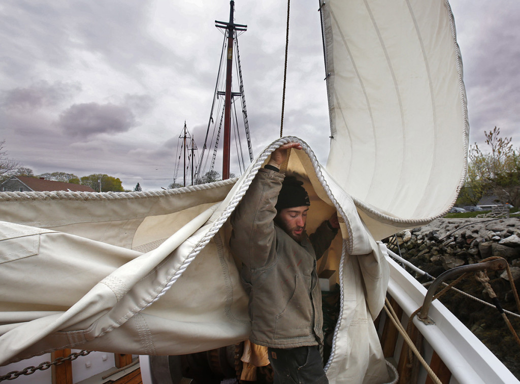 Logan Sampson holds up a sail while preparing the schooner for the sailing season.
