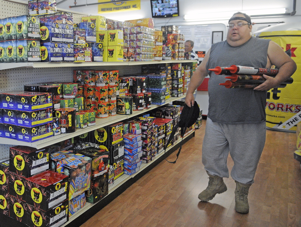 "John Bergen of Somerville carries fireworks Tuesday at the Pyro City store in Manchester. Bergen, a self-described professional explosives engineer, said safety is paramount with fireworks.  ""It's up to the individual to keep it safe so we all can enjoy the tradition,"" he said. This year, shoppers are looking for lots of colors in their fireworks, one store official said."