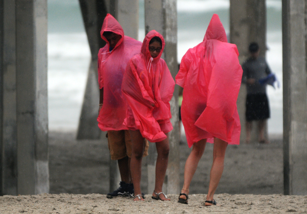 Beachgoers huddle on the beach at Wrightsville Beach, N.C., on Thursday. Residents along the coast of North Carolina are bracing for the arrival of the Hurricane Arthur, a Category 1 storm.