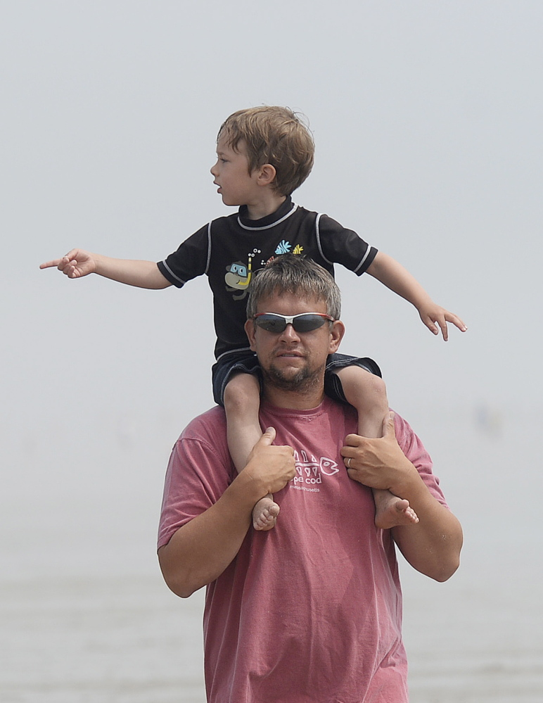 Jason Brown of Barre, Mass., and his son Abraham, 4, look over the sand sculpting competition in Ocean Park on Thursday. More than 60 families participated in the contest.