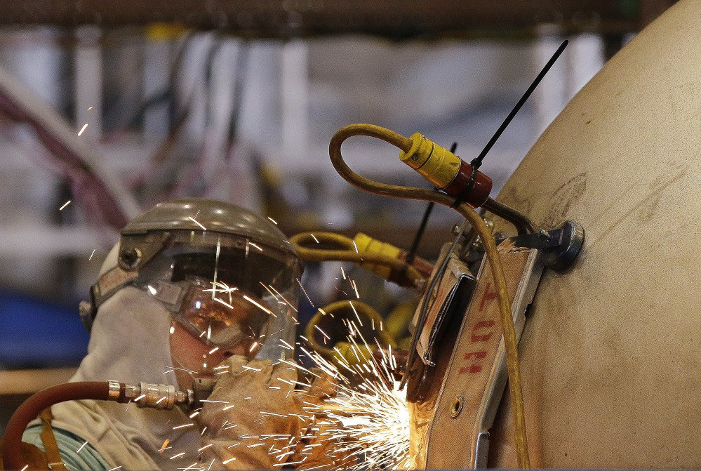 """A welder works on a """"compressed air flask"""" that will eventually be installed in a Virginia-class nuclear-powered submarine at the Electric Boat company's Quonset Point facility in North Kingstown, R.I., this week. The shipyard has hired 2,000 workers in the last four years."""