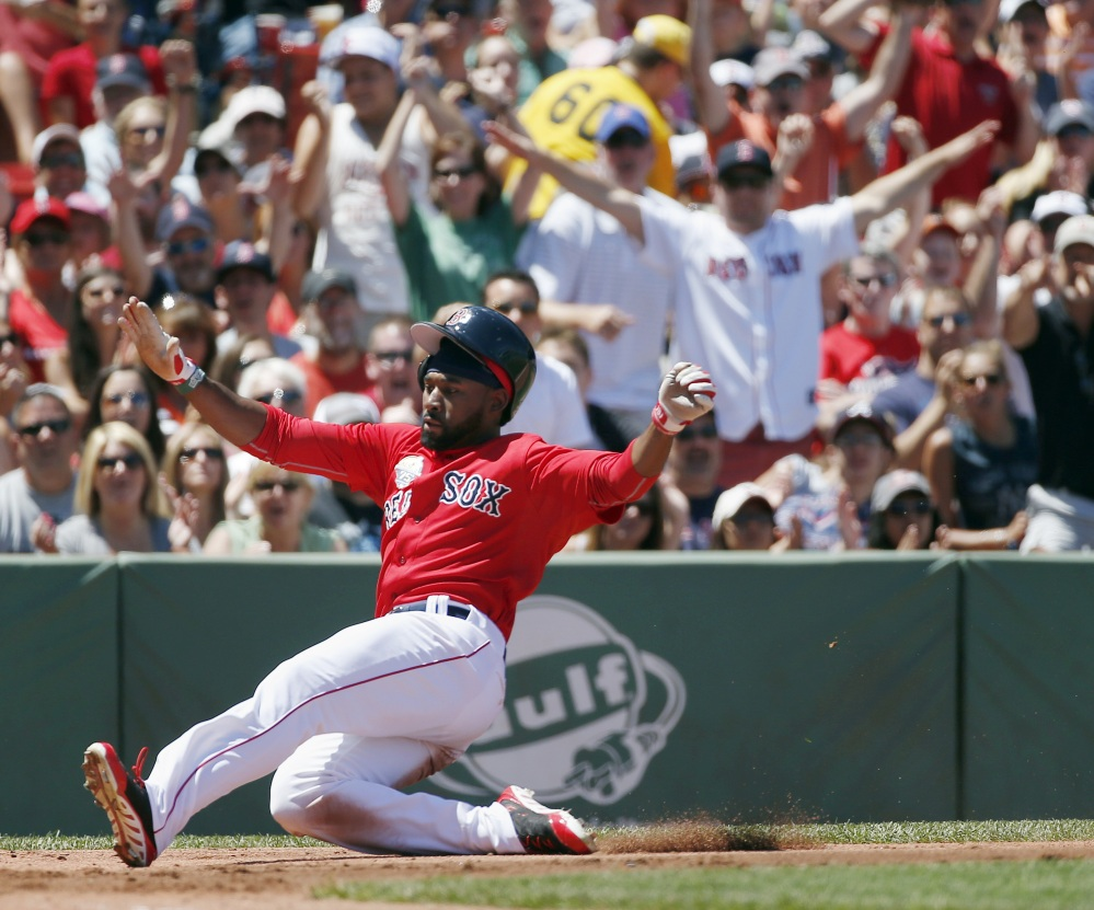 Jackie Bradley Jr. scores on an error by Baltimore's Steve Pearce in the second inning of the first game of a doubleheader Saturday in Boston. The Red Sox won the first game, 3-2.