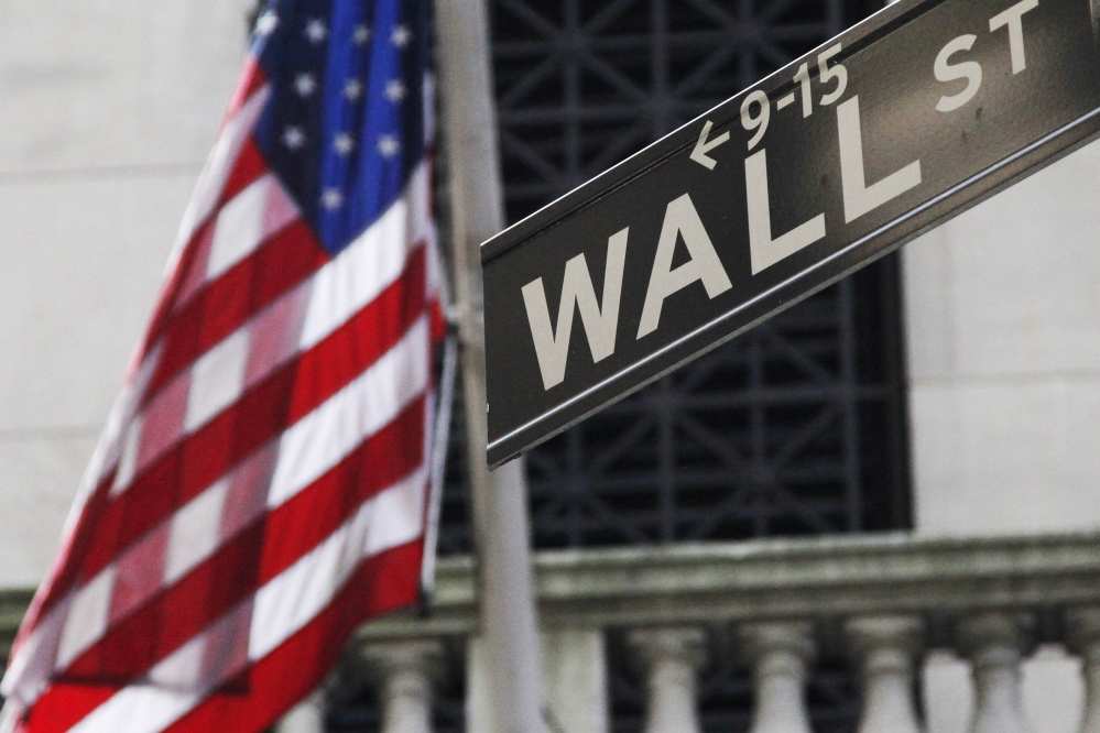 The American flag and a sign for Wall Street outside the New York Stock Exchange.
