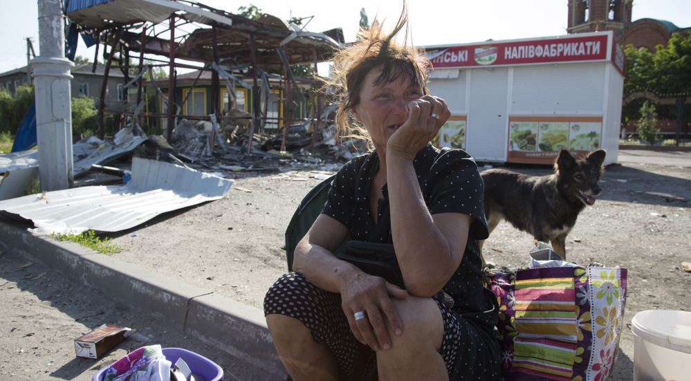 A woman sits near a destroyed shop in the city of Slovyansk, in the Donetsk region of eastern Ukraine, on Saturday. By late afternoon, Ukrainian troops were fully in control of rebel headquarters in Slovyansk, a city of about 100,000.