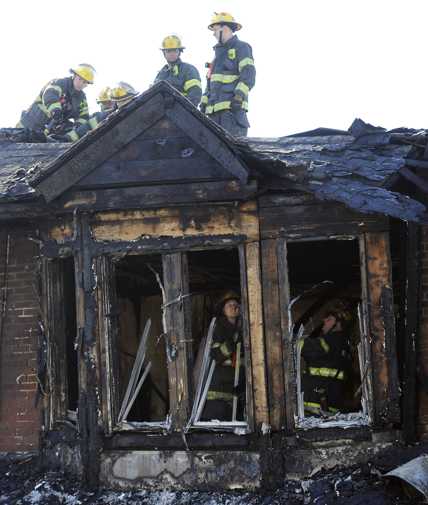 Philadelphia firefighters work on  burned row homes on Saturday in Philadelphia.