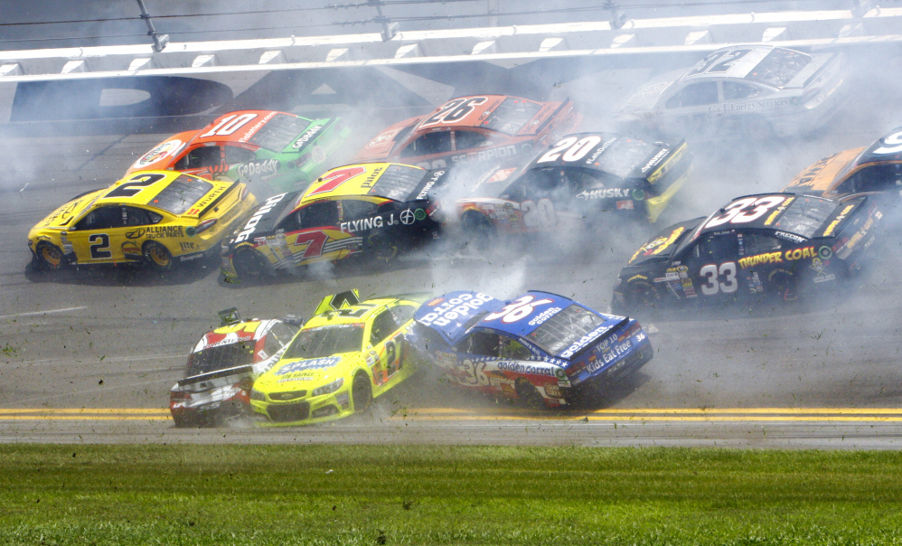 Kasey Kahne, front left, Paul Menard, 27, and Reed Sorenson, 36, are among the cars that crashed coming out of the backstretch going in to turn 3 during the NASCAR Sprint cup Series auto race at Daytona International Speedway in Daytona Beach, Fla., on Sunday