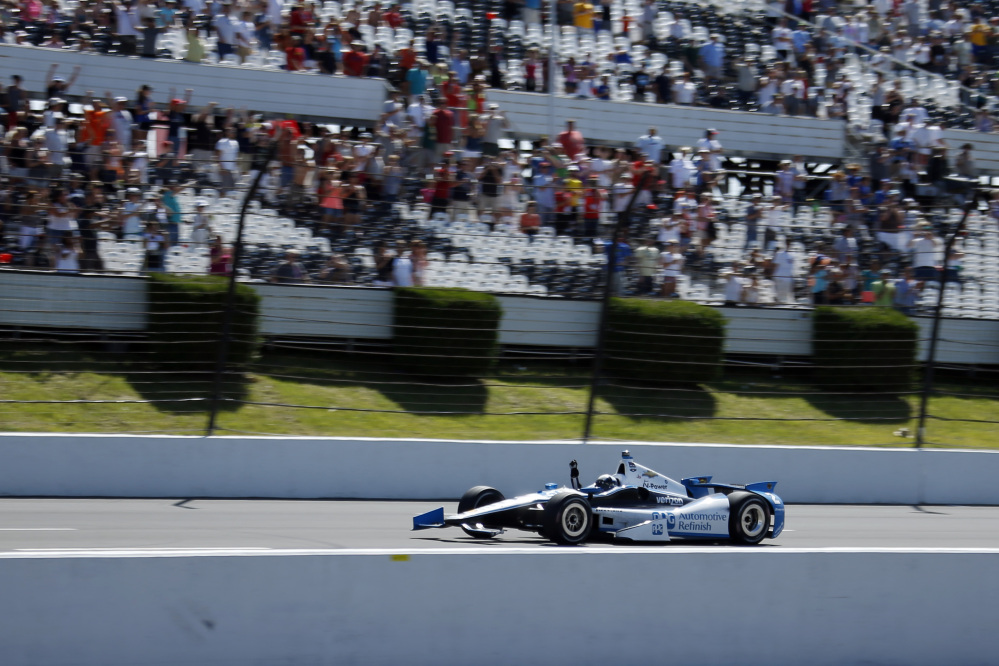 Juan Pablo Montoya, of Colombia, celebrates as he drives down the front stretch to win the Pocono IndyCar 500 auto race on Sunday, in Long Pond, Pa.