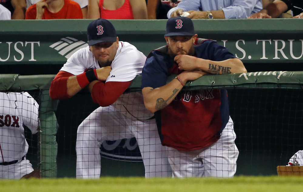 Red Sox catcher A.J. Pierzynski, left, and left fielder Jonny Gomes watch from the dugout in the ninth inning of an 8-3 loss Tuesday night in Boston.
