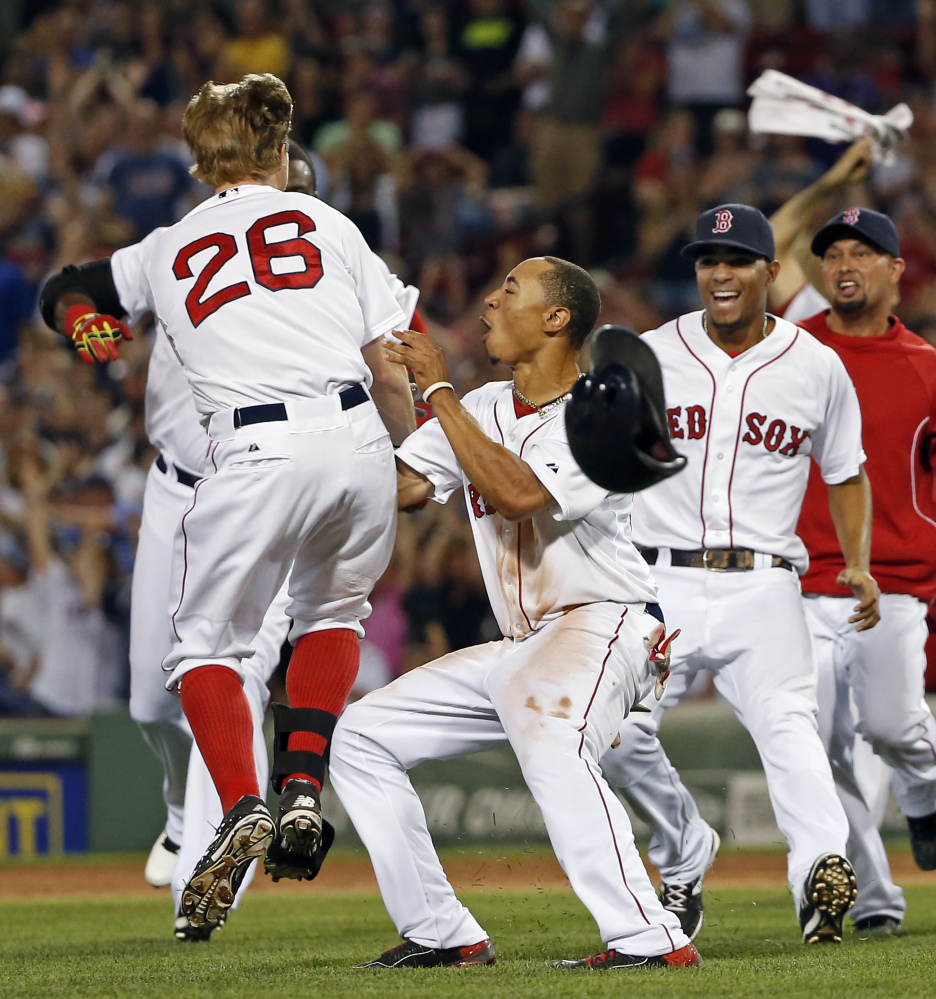 Brock Holt (26) celebrates with teammates including Mookie Betts, front center, and Xander Bogaerts after hitting an RBI single to give the Red Sox a 5-4 win over the Chicago White Sox on Wednesday night.