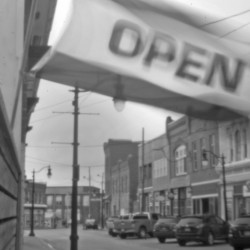 "An ""open"" flag flies above a storefront in Eastport, not far from where the Passamaquoddy's attorney Don Gellers had his office in the early 1960s, before his former legal intern, Tom Tureen, took over as the tribe's representative in the Indian land claims lawsuit."