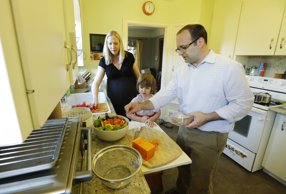 Ryan Carson, right, cooks dinner with his wife, Jenny Roraback-Carson, and their daughter Clara, 3, at their home in Seattle.