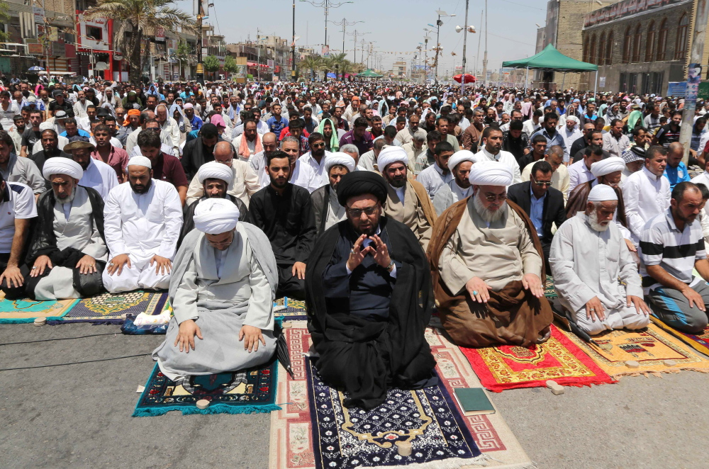 Shiites attend Friday prayers in Baghdad's Sadr City. Meanwhile, a suicide bomber blew himself up at a checkpoint near Kirkuk, killing 13 people and wounding 23.