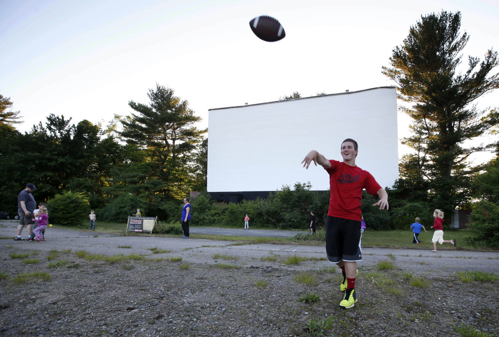 Shawn Smart, on vacation from Athol, Mass., plays catch with a football while waiting for the sun to set at the Saco Drive-In in Saco.