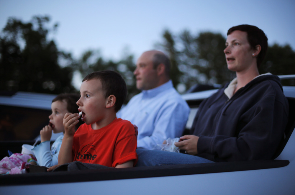 Mike and Naomi Gibel, and their children Norah, 4, left, and Issak, 7, watch a movie from the back of a pick-up truck at the Saco Drive-In in Saco.