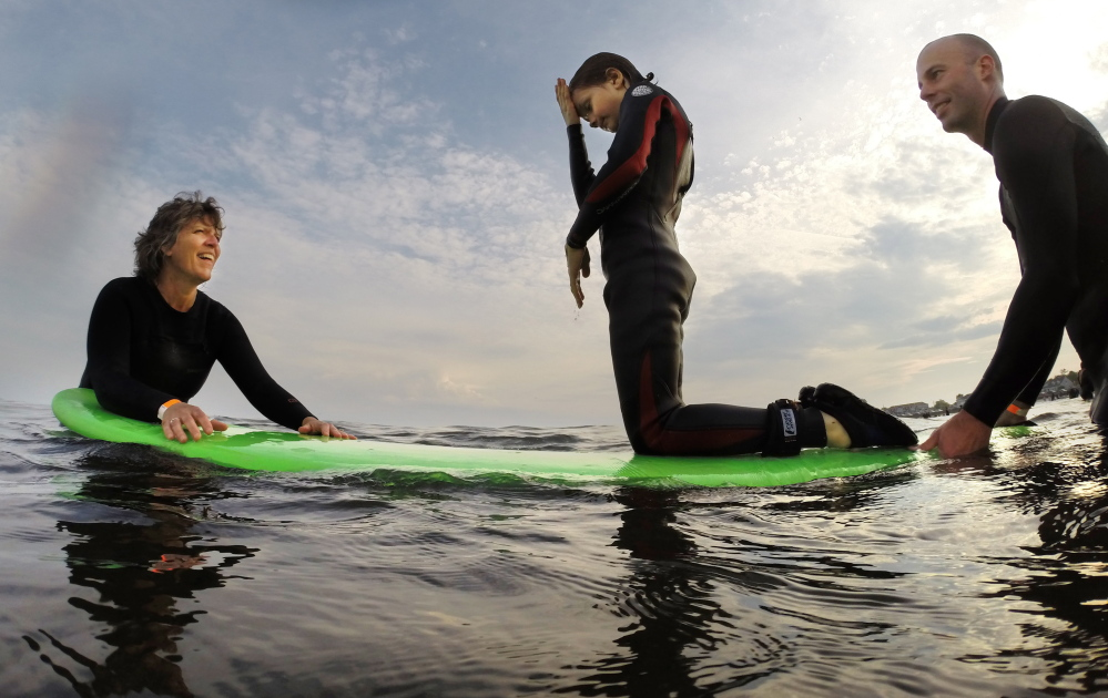 Evan Lamb, 8, of Kittery kneels on a surf board steadied by volunteers Laurie Troy, left, and Jeff Beaudoin. Gregory Rec/Staff Photographer