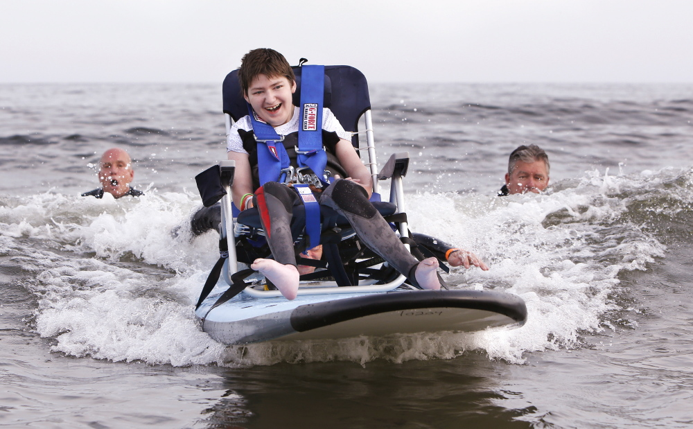 Joseph Shortsleeves, 14, of Biddeford, rides a wave while strapped into a chair. Gregory Rec/Staff Photographer