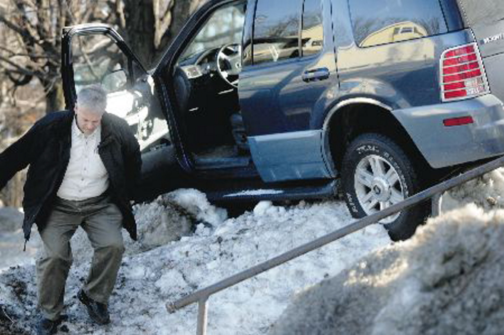 Augusta police Lt. Keith Brann leaps from an SUV he turned off after it became lodged in a snowbank in February 2010 on Western Avenue in Augusta.
