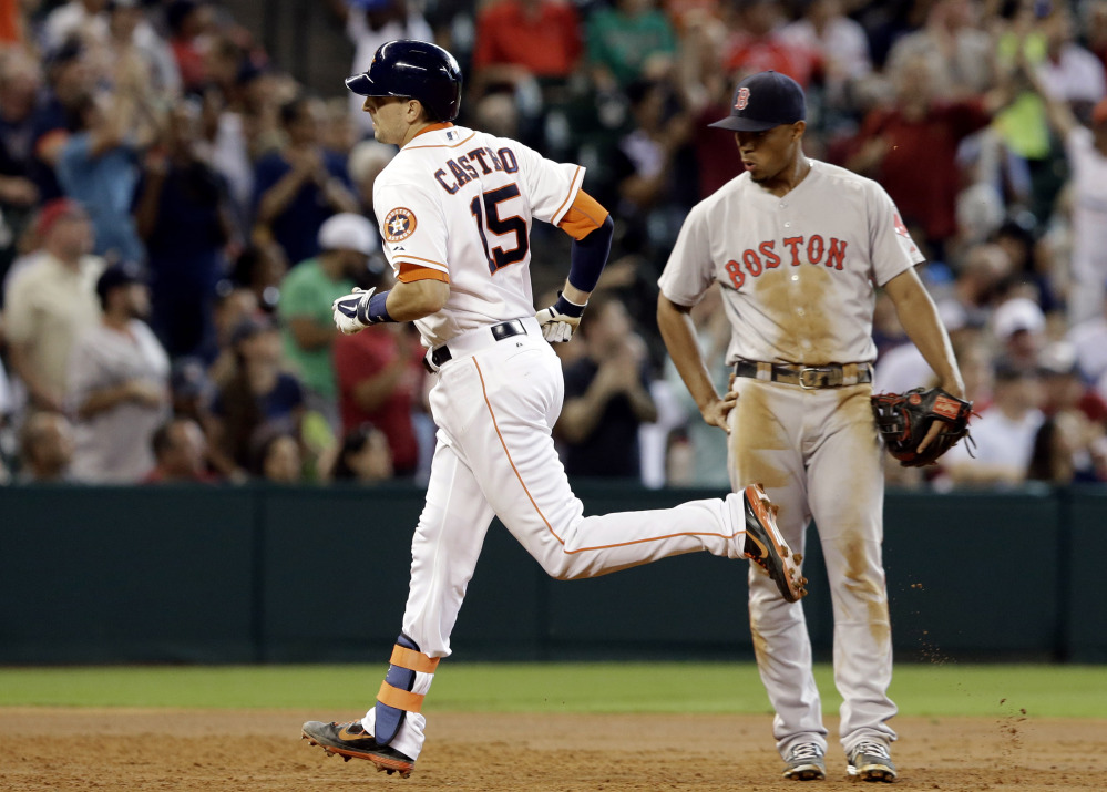 Astros catcher Jason Castro rounds the bases in front of Red Sox third baseman Xander Bogaerts after hitting a two-run home run in the third inning Saturday in Houston.