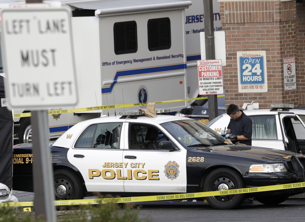 A Jersey City Police Department cruiser is seen with its back window shattered as officials investigate the scene where a Jersey City Police Department officer was shot and killed while responding to a call at a 24-hour pharmacy on Sunday.