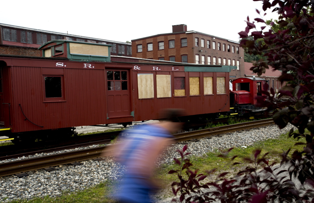A runner makes his way past a train car belonging to the Narrow Gauge Railroad that is boarded up after it was vandalized. The director of the railroad company and museum says damage is estimated at more than $3,800.