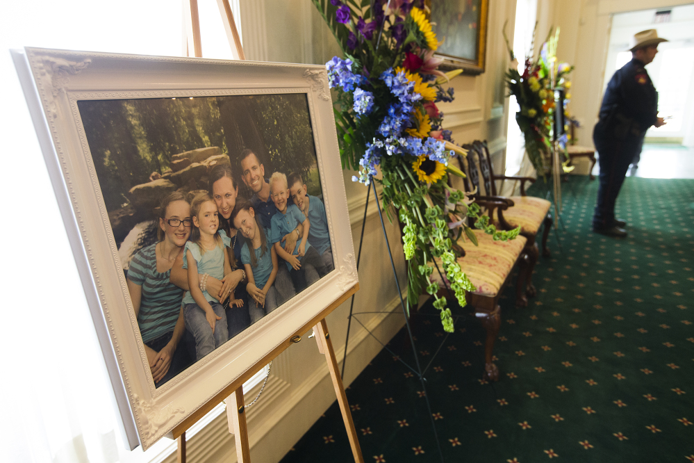 A family portrait of the Stephen and Katie Stay family is on display before visitation at Klein Funeral Home on Tuesday in Houston.