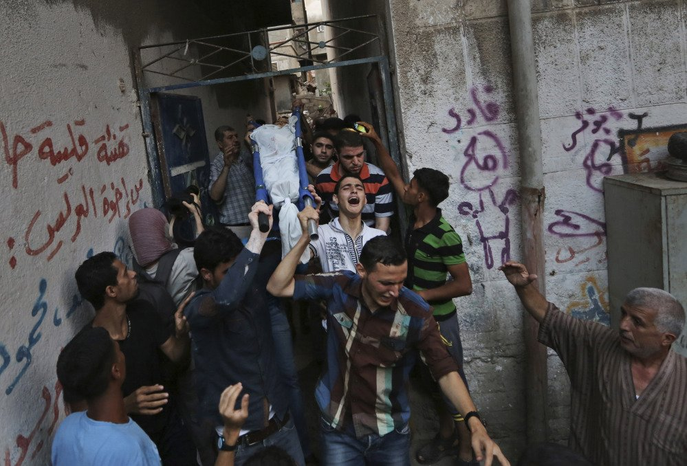 Mourners carry a Palestinian boy, one of three children killed by an Israeli missile strike earlier, outside the family house during their funeral in Gaza City on Thursday. The children were killed while feeding pigeons on the roof of their house in the Sabra neighborhood of Gaza City, the family said.