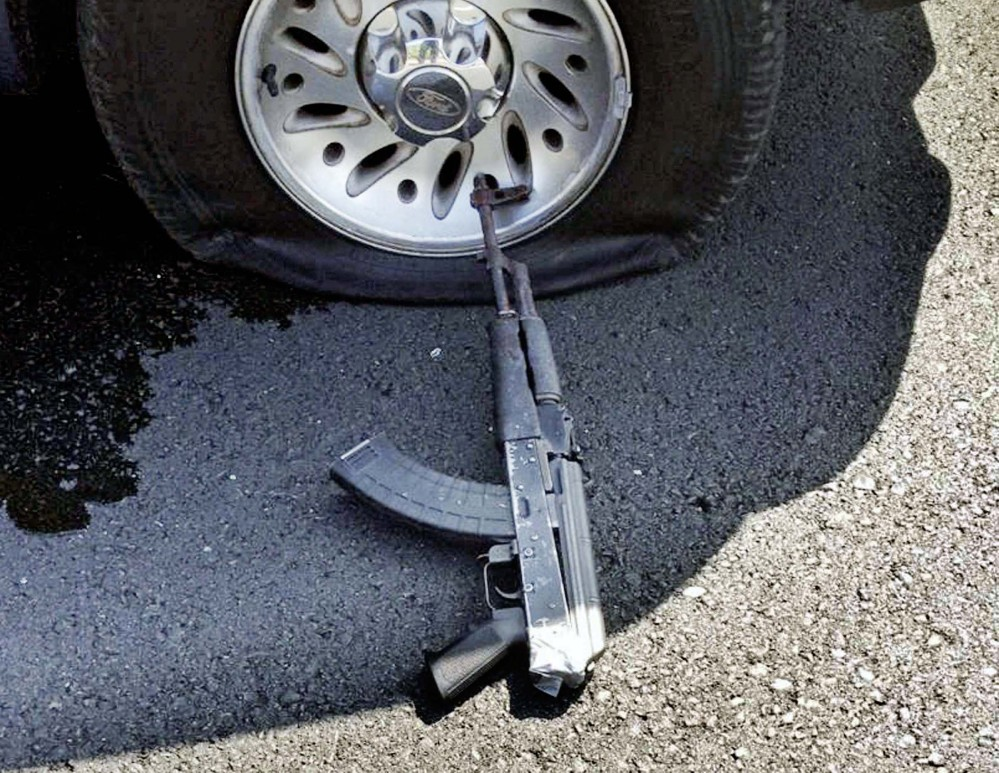 In the aftermath of the Stockton, Calif., robbery, a tire on the robbers' car is shown shot out and a firearm lies on the ground.