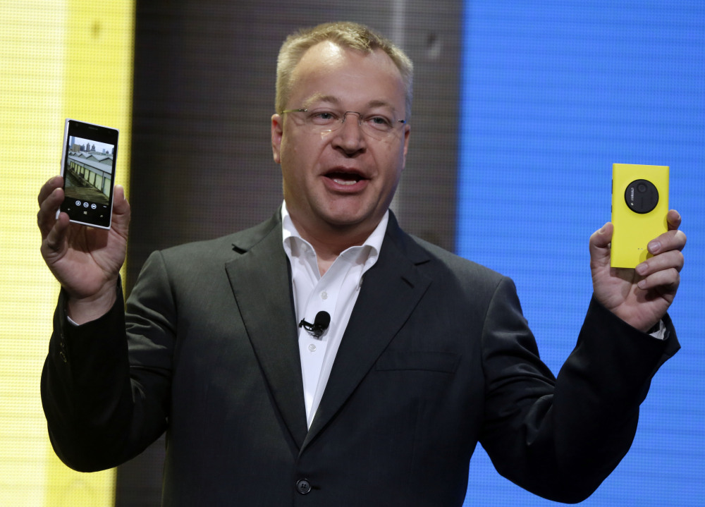 Then-Nokia CEO Stephen Elop shows the company's Nokia Lumia 1020 in New York in 2013. Elop, now Microsoft's executive vice president, sent employees a memo detailing its job cut plans. Microsoft on Thursday said it will cut up to 18,000 jobs over the next year, with about 12,500 related to Microsoft's acquisition of Nokia's phone business in April.