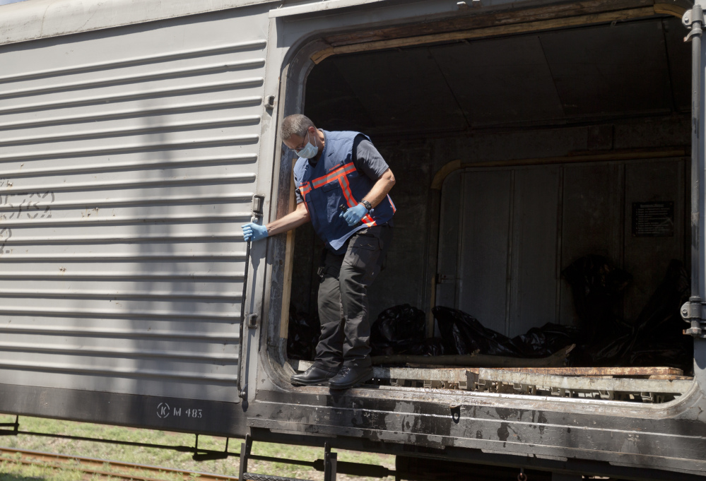 Peter Van Vilet, team leader of Netherlands' National Forensic Investigations Team exits a carriage while inspecting a refrigerated train loaded with the bodies of passengers moved from the crash site of Malaysia Airlines Flight 17, located 15 kilometers (9 miles) away, in Torez, eastern Ukraine, Monday, July 21, 2014. Another 21 bodies have been found in the sprawling fields of east Ukraine where Malaysia Airlines Flight 17 was downed last week, killing all 298 people aboard. (AP Photo/Vadim Ghirda)