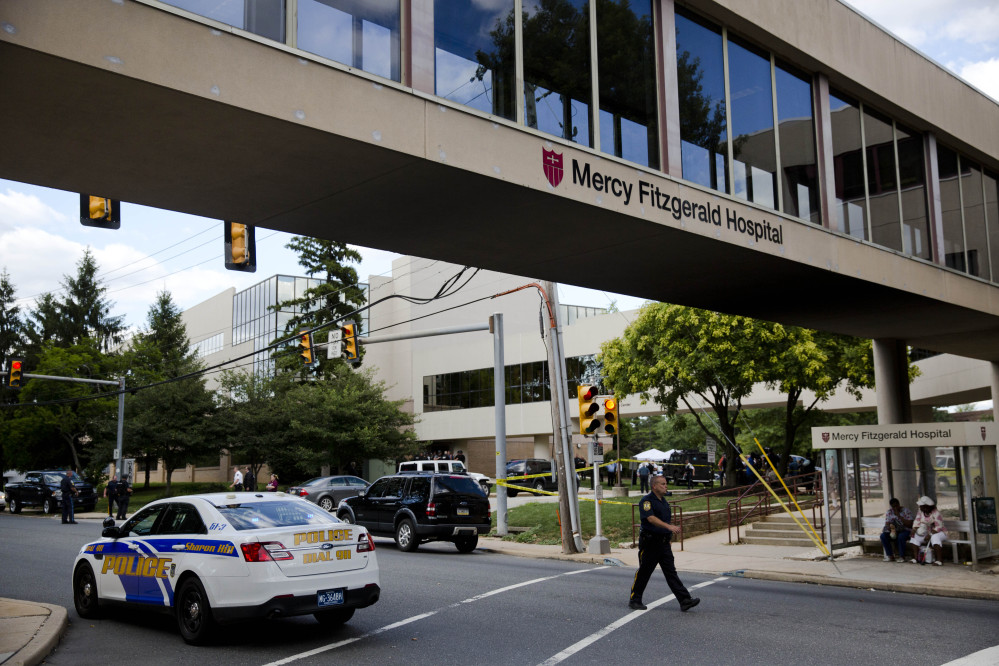 An officer walks near the scene of a shooting Thursday at Mercy Fitzgerald Hospital in Darby, Pa. A shooting at a suburban Philadelphia hospital campus killed one worker and injured two other people.