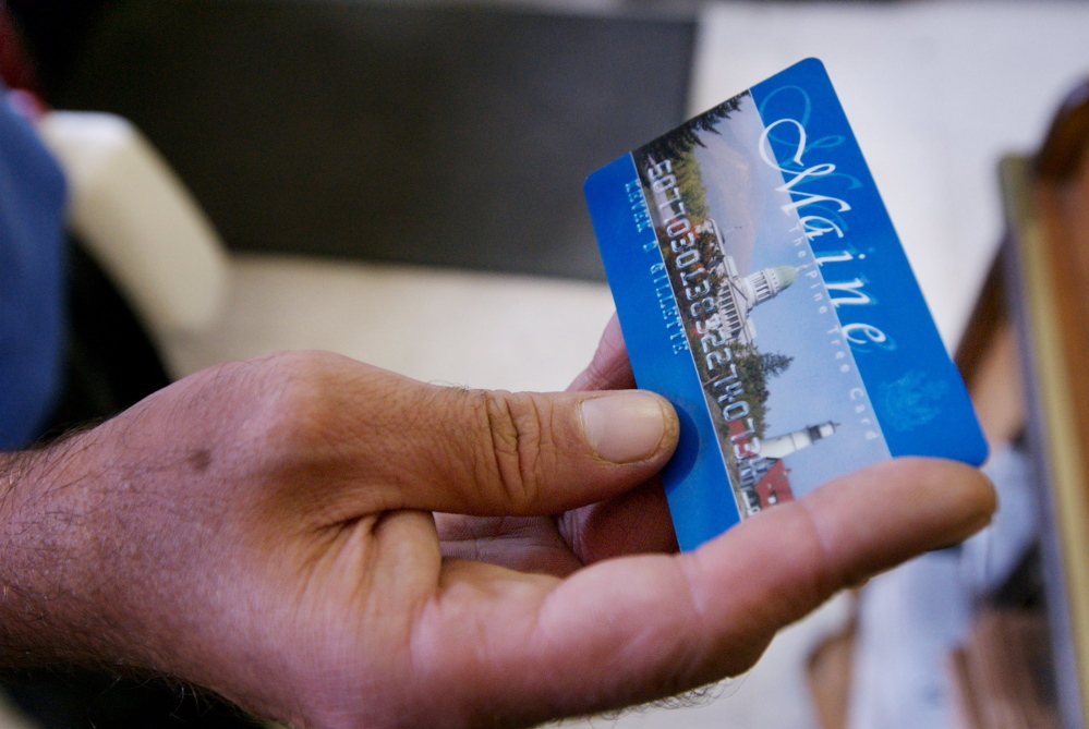 A Portland man uses a magnetic food stamp card to pay for his groceries in 2008. Gov. Paul LePage is proposing a ban on food stamps for anyone convicted of a drug felony in the past two decades.