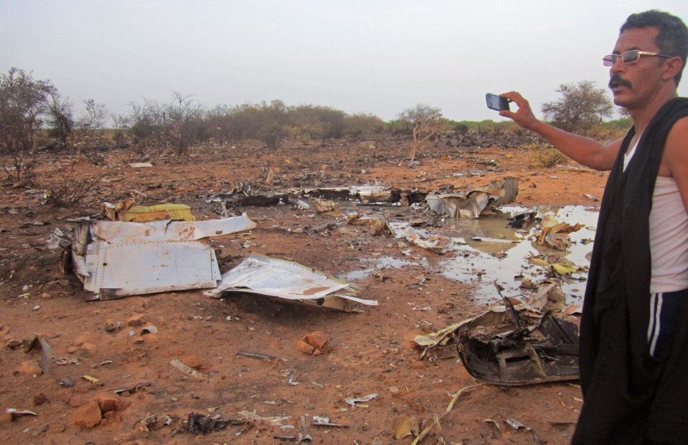 This photo provided by the Burkina Faso Military shows a man at the site of the Air Algerie plane crash in Mali. At least 116 people were killed in Thursday's disaster, nearly half of whom were French.