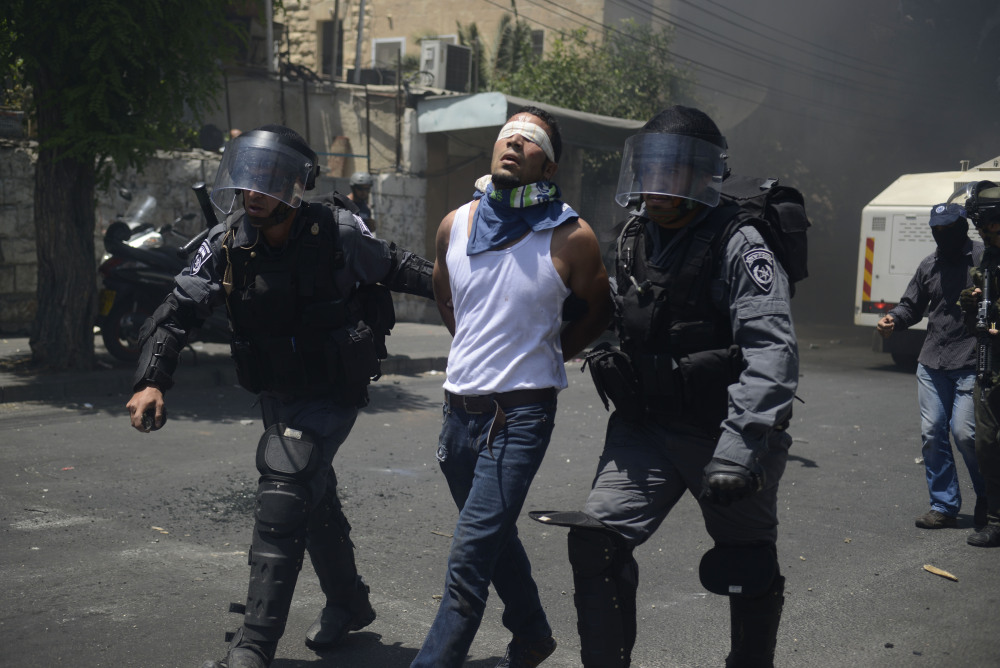 Israeli police officers detain a Palestinian man during clashes near Jerusalem's Old City on Friday.