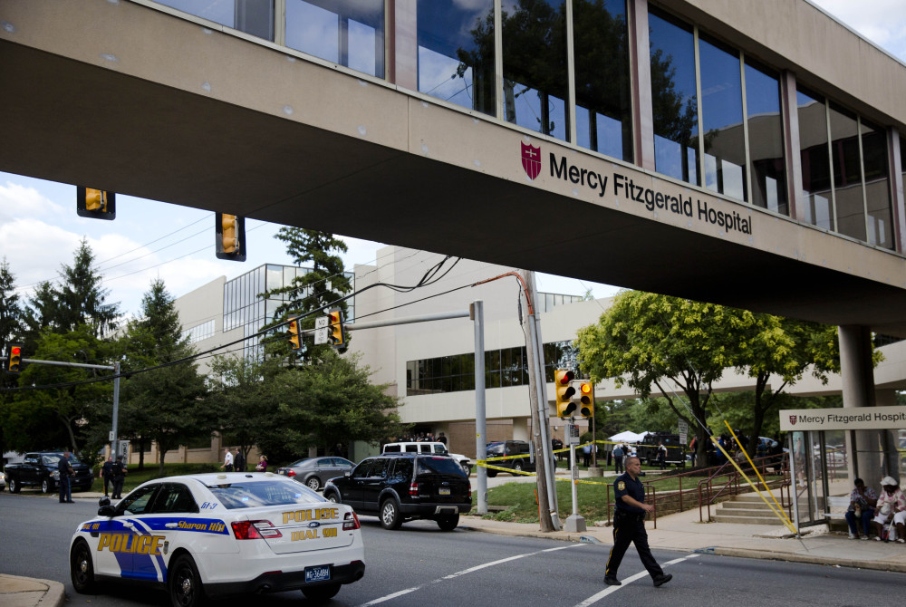 An officer walks near the scene of a shooting Thursday at Mercy Fitzgerald Hospital in Darby, Pa. The shooting at the suburban Philadelphia hospital campus killed one worker.